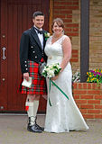 Scottish wedding. Photo of a traditional scottish wedding bride and groom wearing tartan kilt and sgian dubh dagger in sock and holding marriage certificate! royalty free stock images