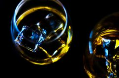 Scottish whiskey in a glass with ice cubes, golden color whiskey. Exclusive drink stock images