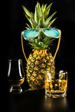 Scottish whisky in a glass with pineapple, golden color whiskey. Exclusive drink stock images