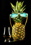 Scottish whisky in a glass with pineapple, golden color whiskey. Exclusive drink royalty free stock photo