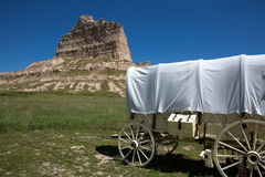 Scotts Bluff National Monument Nebraska. A covered wagon sits by Scotts Bluff National Monument depicting how settlers passed through the area on their migration Royalty Free Stock Photography