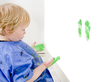 Scoundrel. A young boy examining his mischief - the green hand prints he just made on a wall Stock Image