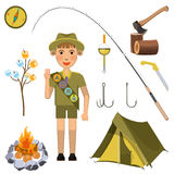 Scout boy with hand honor sign near camp equipment set Royalty Free Stock Image