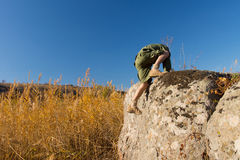 Scout Climbing on Big Rock at the Field Royalty Free Stock Image
