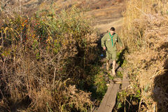 Scout crossing a narrow footbridge over a stream Stock Photography