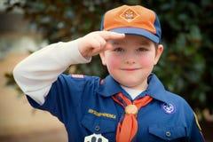 Scout de CUB donnant le salut de scout de garçon Photo stock