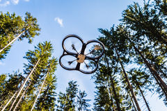 Scout drone in the forest. A small spy quad copter scout drone flying through the trees in a forest stock image