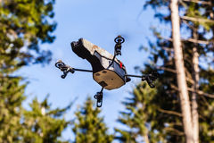Scout drone in the wild. A small spy quad copter scout drone flying through the trees in a forest royalty free stock photos