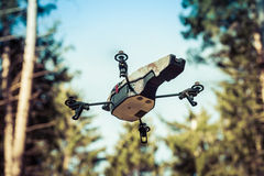 Scout drone in the wilderness. A small spy quad copter scout drone flying through the trees in a forest royalty free stock photos