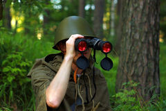 Scout in forest. Scout in summer forest in a helmet with binoculars Royalty Free Stock Image