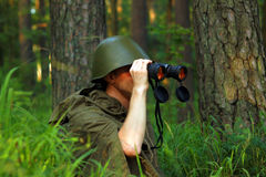 Scout in forest. Scout in summer forest in a helmet with binoculars Royalty Free Stock Photos
