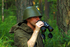 Scout in forest. Scout in summer forest in a helmet with binoculars Royalty Free Stock Photo