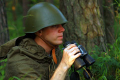Scout in forest. Scout in summer forest in a helmet with binoculars Stock Photo