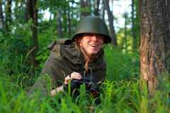 Scout in forest. Scout in summer forest in a helmet with binoculars Stock Image