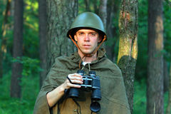 Scout in forest. Scout in summer forest in a helmet with binoculars Stock Photos
