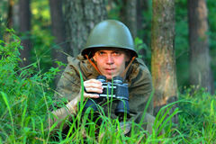 Scout in forest. Scout in summer forest in a helmet with binoculars Stock Photography