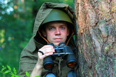 Scout in forest. Scout in summer forest in a helmet with binoculars Royalty Free Stock Images