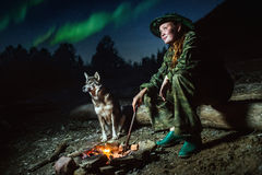 Scout girl with her dog around campfire at night  stars and aurora borealis Royalty Free Stock Photo