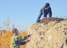 Scout helping a young boy rock climbing. Giving him a helping hand from below as he learns about the wilderness and nature Royalty Free Stock Photos