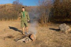 Scout ou garde forestière faisant un feu à cuire Photographie stock libre de droits