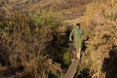 Scout or ranger crossing a log bridge Stock Photos