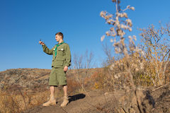 Scout standing on a rock taking a compass reading Royalty Free Stock Photography