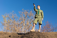Scout standing on a rock taking a compass reading Stock Images