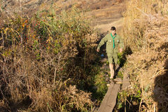 Scout stepping over a boardwalk bridge. Scout stepping carefully over a narrow boardwalk bridge over a river or ravine as he negotiates a wilderness trail, high Royalty Free Stock Photos