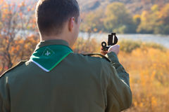 Scout taking a sighting with his compass Royalty Free Stock Photography