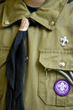 Scout uniform detail. Closeup of a scout uniform. Lily symbols and tie, washed green fabric Stock Photos