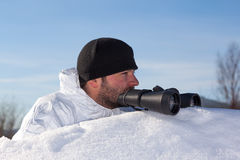 Scout in white camouflage coat with binoculars Stock Photo