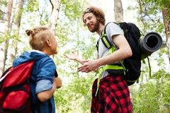 Scouts in the forest. Young men explaining his buddy how to find the road to suitable place for living during their backpack trip Stock Images