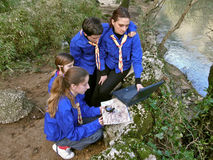 Scouts are oriented with laptop. Scouts (best friends) with laptop, map and compass near the river learning orienteering in nature. Horizontal color photo stock photos
