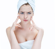 Scowling girl pointing at her acne with a towel on her head. Woman skin care concept / photos of ugly problem skin girl on white background royalty free stock photography