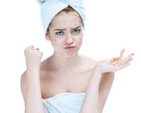 Scowling girl in shock of her acne with a towel on her head. Stock Image