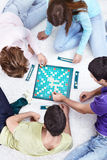 Scrabble. Young people play scrabble on the carpet Stock Photo