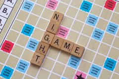 Scrabble board game with the scrabble tile spell `Game Night`. On a table royalty free stock image