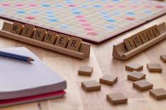 Scrabble board game with the scrabble tile spell `Winner Loser`