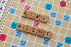 Scrabble board game with the scrabble tile spell `Game Night`. On a table stock photography