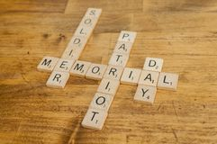 Scrabble Letter Tiles Memorial Day Patriotic Holiday. Scrabble letter tiles spelling out words associated with memorial day including patriotic, soldier Royalty Free Stock Photography