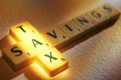 Scrabble letters spelling tax savings stock photos