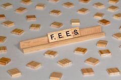 Scrabble tiles spelling Fees. Scrabble Word Game wood tiles spelling Fees on a white background royalty free stock images