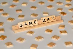 Scrabble tiles spelling Game Day. Scrabble Word Game wood tiles spelling Game Day on a white background royalty free stock photo
