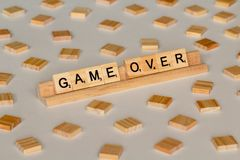Scrabble tiles spelling Game Over. Scrabble Word Game wood tiles spelling Game Over on a white background stock photography