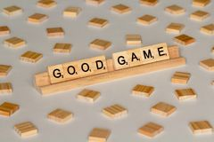 Scrabble tiles spelling Good Game. Scrabble Word Game wood tiles spelling Good Game on a white background stock images