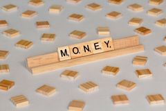 Scrabble tiles spelling Money. Scrabble Word Game wood tiles spelling Money on a white background royalty free stock photography