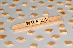 Scrabble tiles spelling Words. Scrabble Word Game wood tiles spelling Words on a white background royalty free stock photo