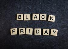 Scrabblebokstavstegelplattor på svart kritiserar bakgrund som stavar Black Friday arkivfoto