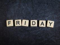 Scrabblebokstavstegelplattor på svart kritiserar bakgrund som stavar fredag arkivfoto
