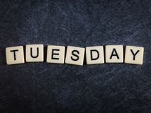 Scrabblebokstavstegelplattor på svart kritiserar bakgrund som stavar tisdag arkivfoto